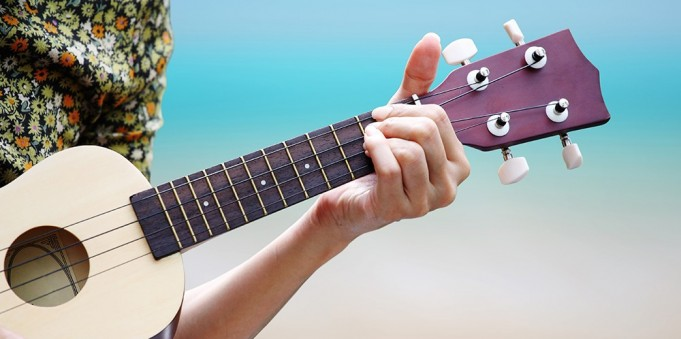 hand picking Guitar ,Ukulele on the beach.